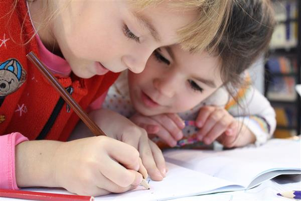 Two Pre-school children drawing together